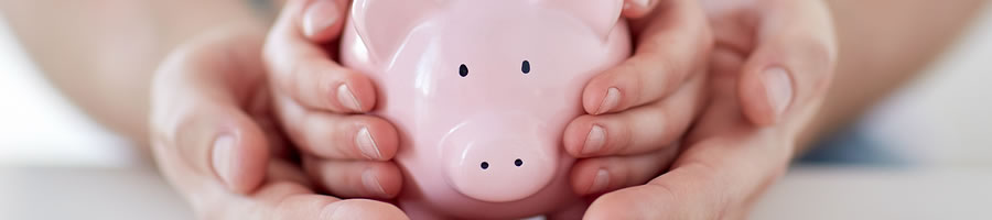 Savings Accounts Options From Wheat State Credit Union - Image of a child holding a piggy bank with the parent's hands securing the child's hands